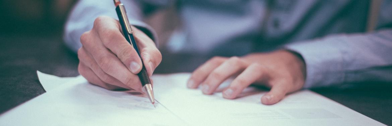 Person die einen Vertrag unterschreibt